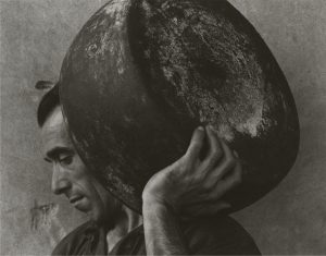 Paul Strand photo of a worker carrying a large Parmesan cheese wheel