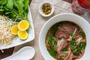 Pho, a Vietnamese rice noodle soup with spiced beef broth and slices of rare steak and condiments such as basil, bean sprouts and lime.
