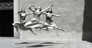 A photograph of three women dancers leaping in mid-air.