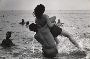 This photo depicts a man lifting a woman over the waves at Coney Island beach.