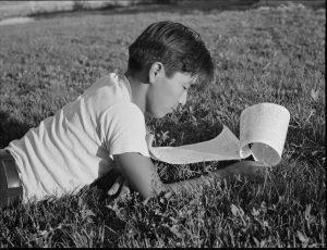 Photo of Japanese boy reading outdoors