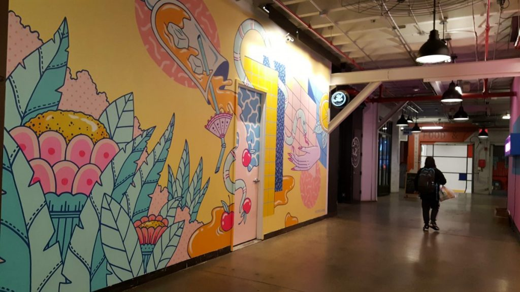 Within the Industry City Food Hall is a work of art featuring an artist - Photo credit by Laura Ng