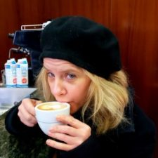 Photo of white woman sipping coffee while wearing a black beret and sweater