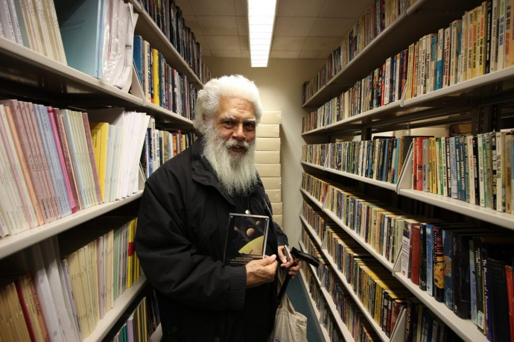 Photo of Samuel L. Delany, an older Black man with a long gray beard, holding a copy of one of his books in the City Tech Library science fiction collection. He wears all black and carries a black cane, a pleased look on his face