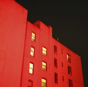 Apartment building with red light shined on it