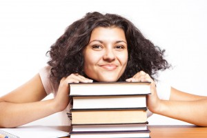a stock image of young woman with her chin on a stack of books