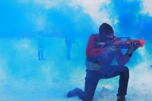 a person crouched with a toy gun
