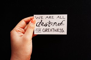"a card that says ""We are all destined for greatness"""