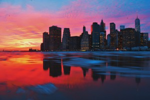 a colorful sunset on the water, by a city skyline