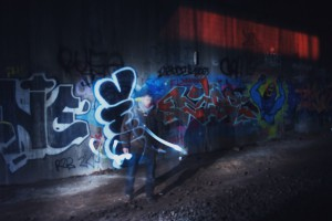 a person standing in front of graffiti