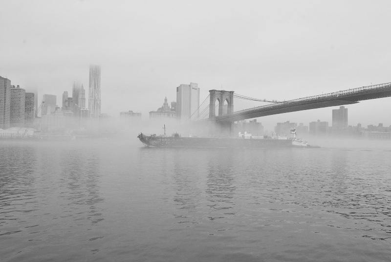 fog covering a ship sailing under a bridge