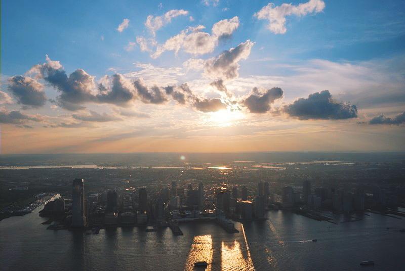 sunny clouds over a city shoreline