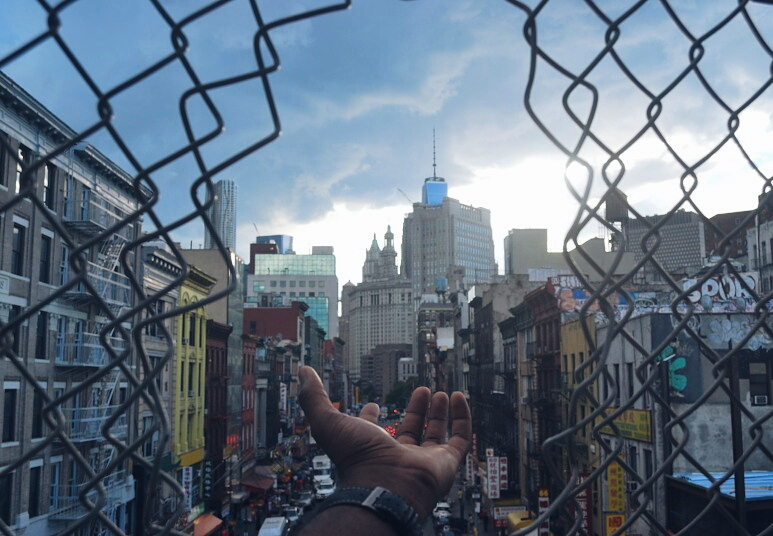 a hand reaching through a hole in a wire-mesh fence