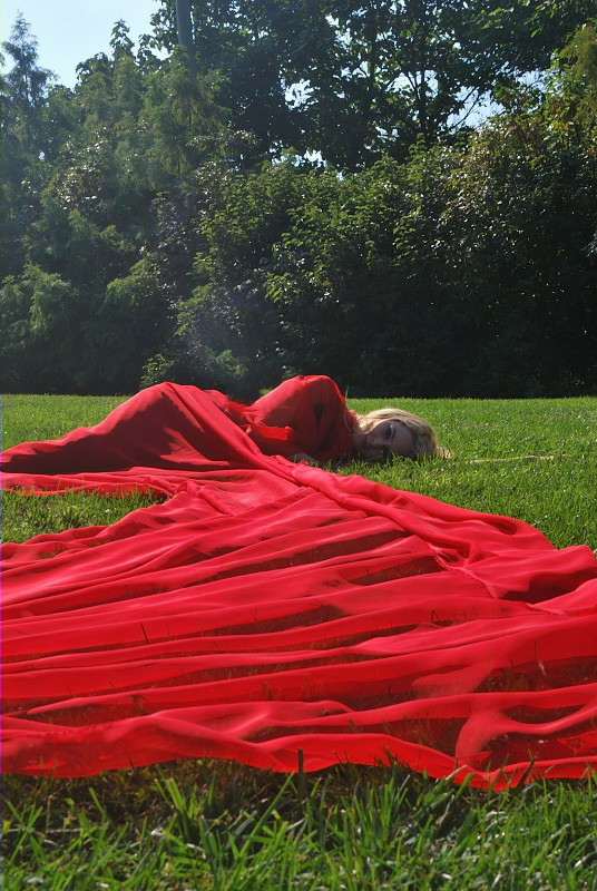 a woman lying on a field, wrapped in red fabric