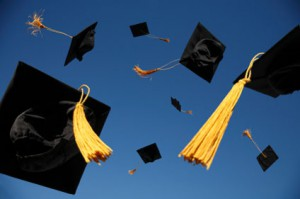 a stock image of graduation hats with tassels being tossed into the air