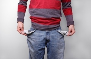 the mid-section of a man holding out his empty jeans pockets