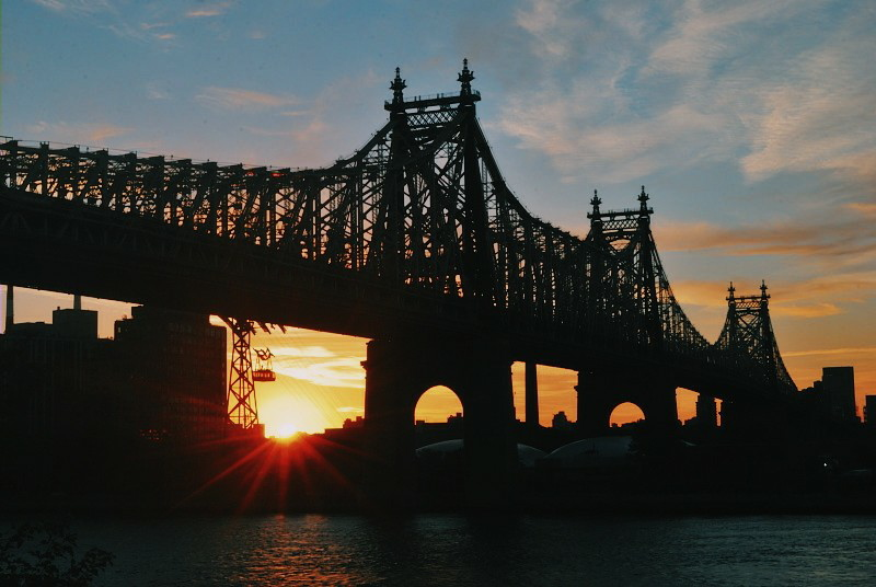sunrise behind a city bridge