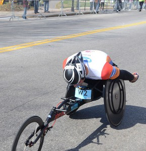 a man running a marathon in a three-wheeled wheelchair