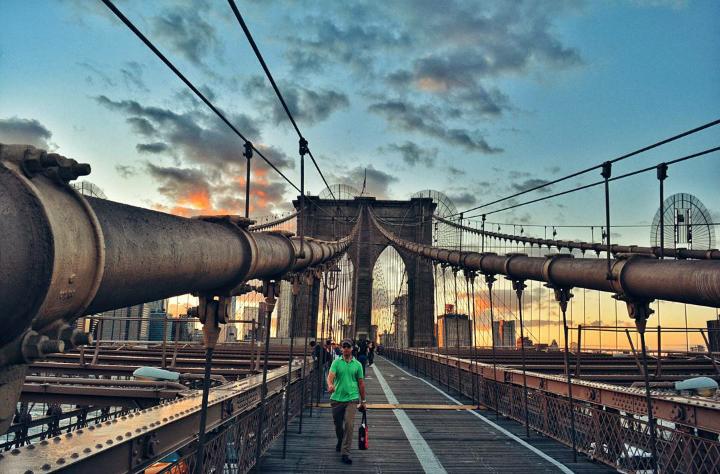people walking on a city bridge