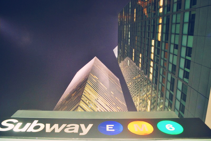 city skyscrapers and a subway sign, from the ground