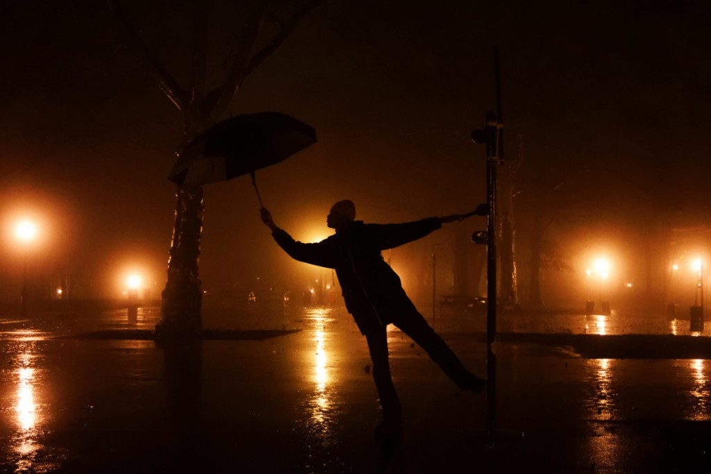 a person holding an umbrella in a park at night