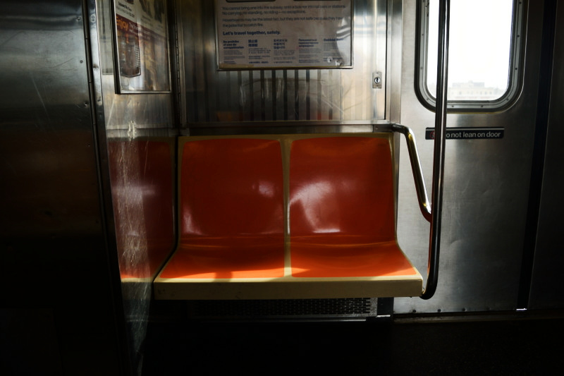 two orange seats on a subway train
