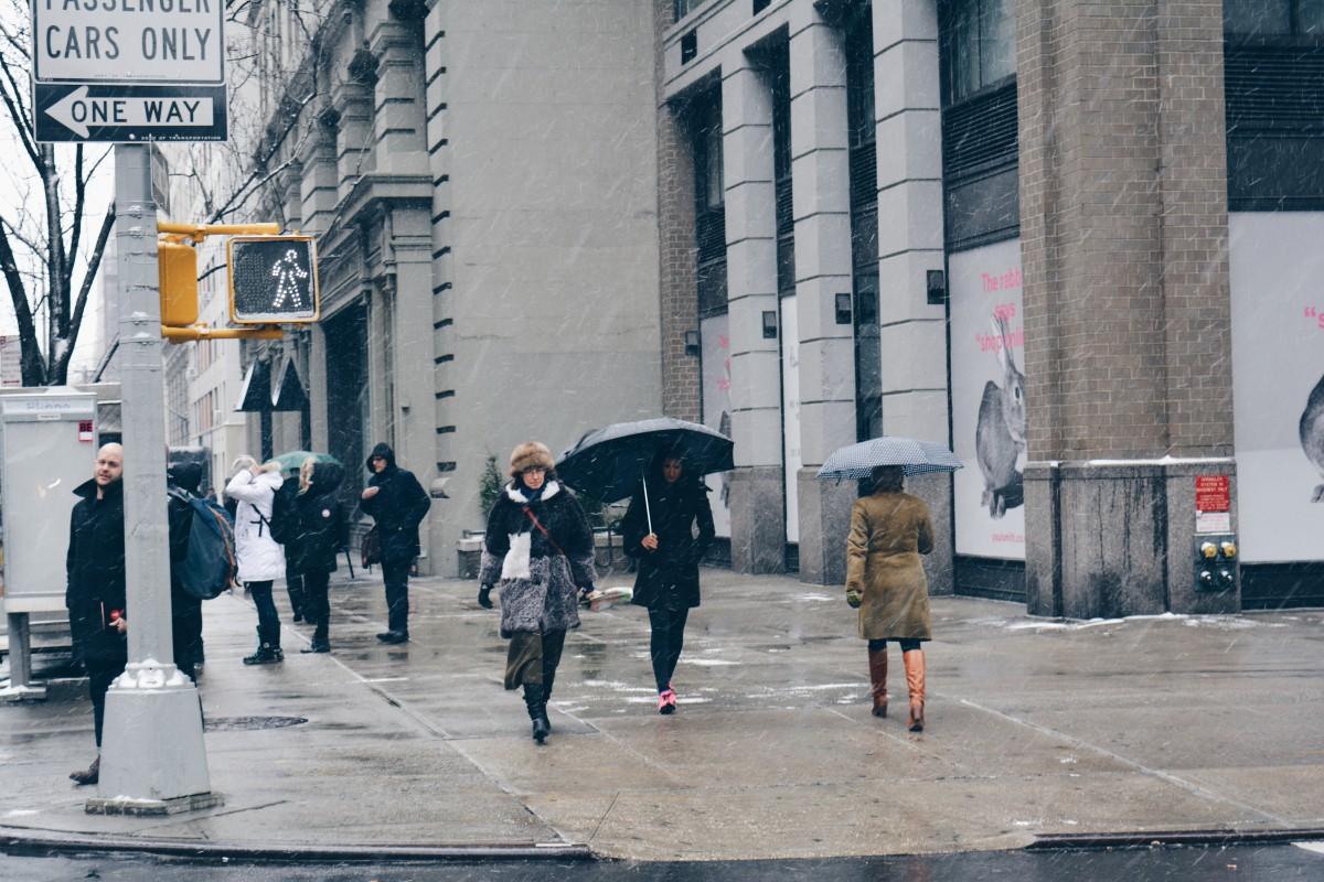 people walking on a sidewalk in the rain