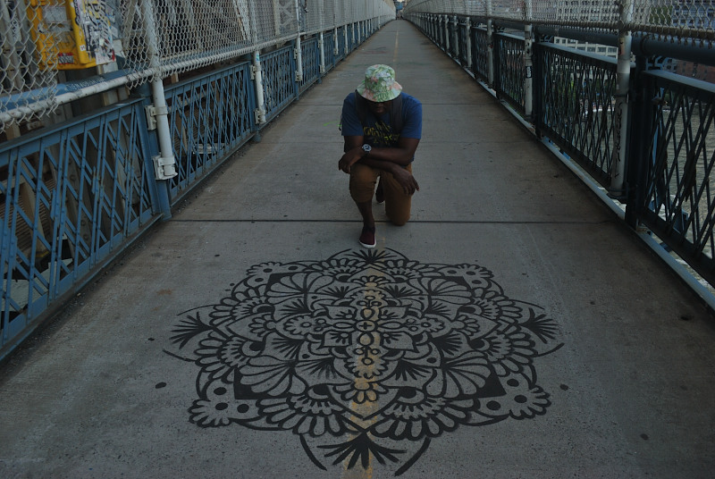 a young man of color in a white hat, kneeling in front of a sidewalk drawing of a black floral shape, on a bridge walkway