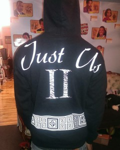 "the back of a man wearing a black sweatshirt that says ""Just Us II"" in white letters"