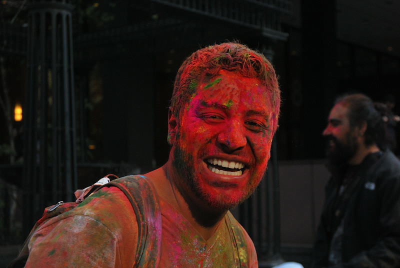 a young man covered in paint, smiling