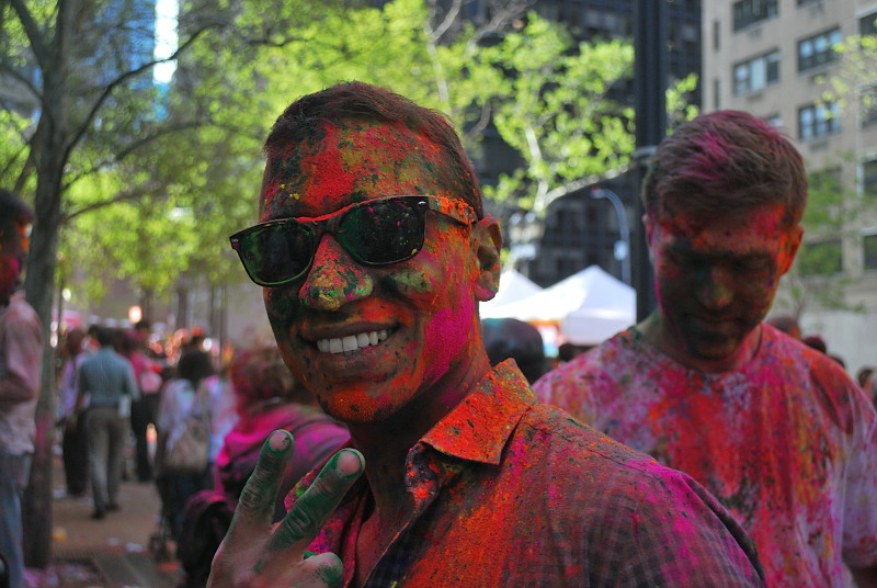 Man in sunglasses, covered in colored paint
