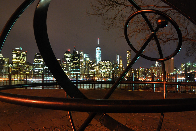 a city skyline at night, behind a sculpture