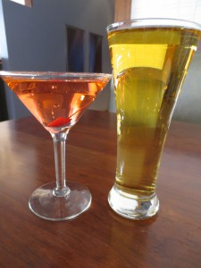 a pink drink in a martini glass and a glass of beer