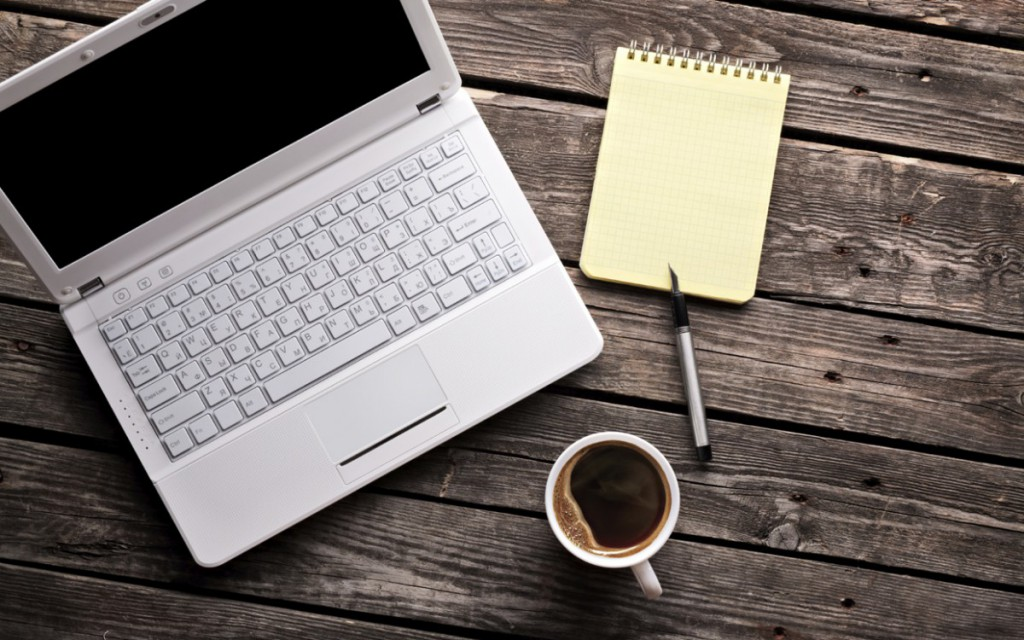 a laptop with a notebook, pen, and a mug of coffee