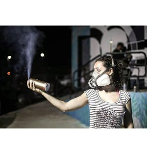 a young woman in a gas mask, spraying an aerosol can