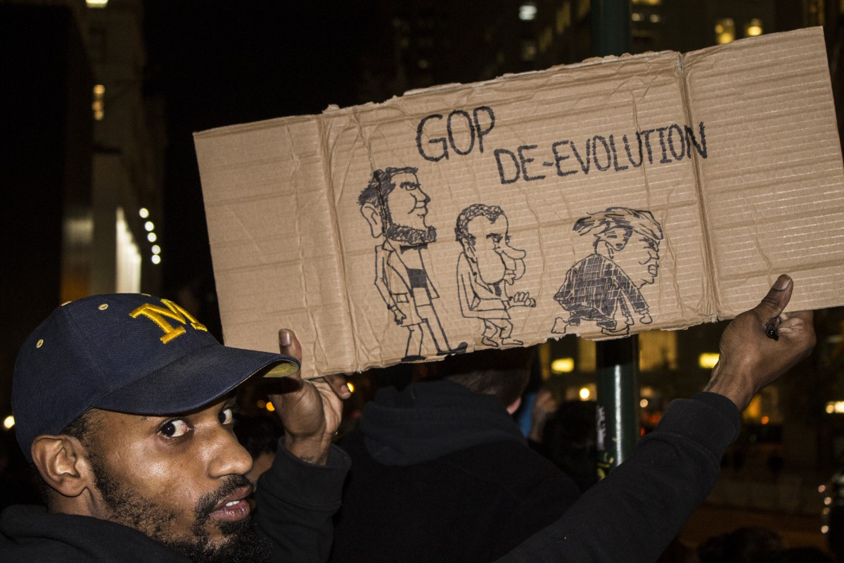 "A protester holding a cardboard sign that says ""GOP DE-EVOLUTION"""
