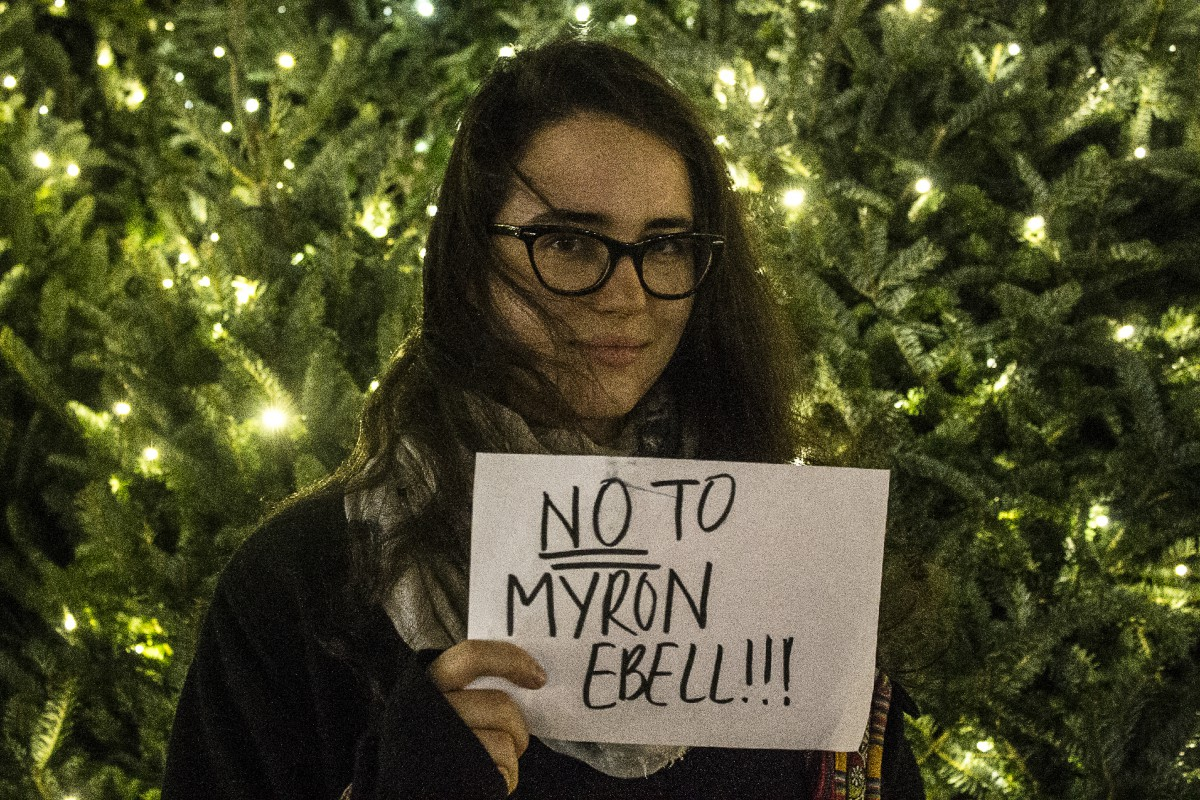 "a woman in glasses holding a sign that says ""NO TO MYRON EBELL!!!"""