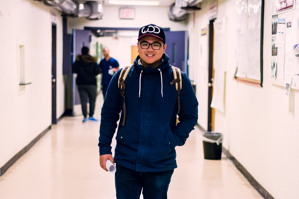 a young man in a jacket wearing a backpack, and a baseball cap