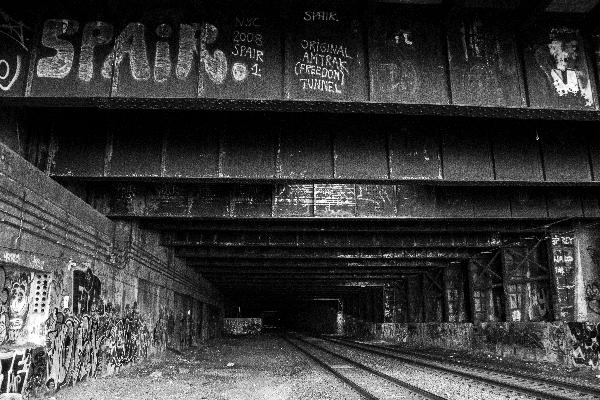 graffiti over train tracks, in black and white