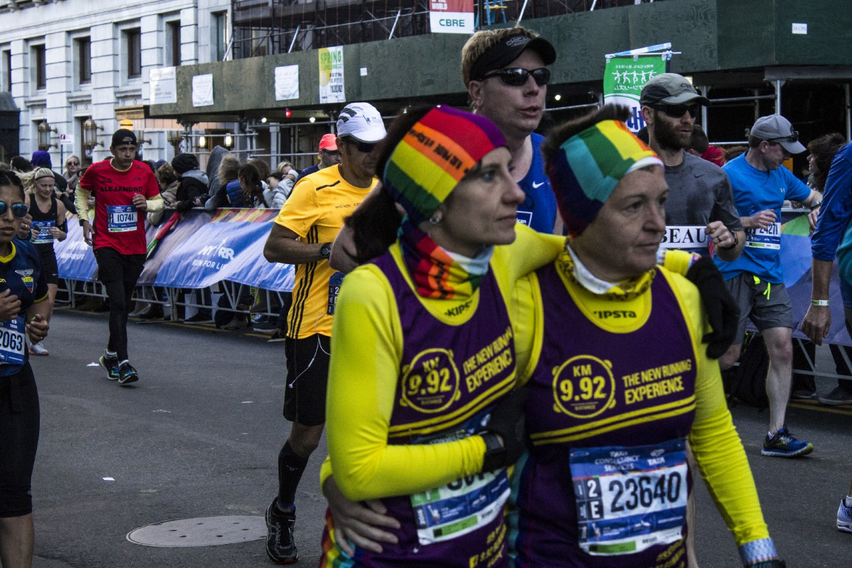 two women running the marathon in rainbow hats