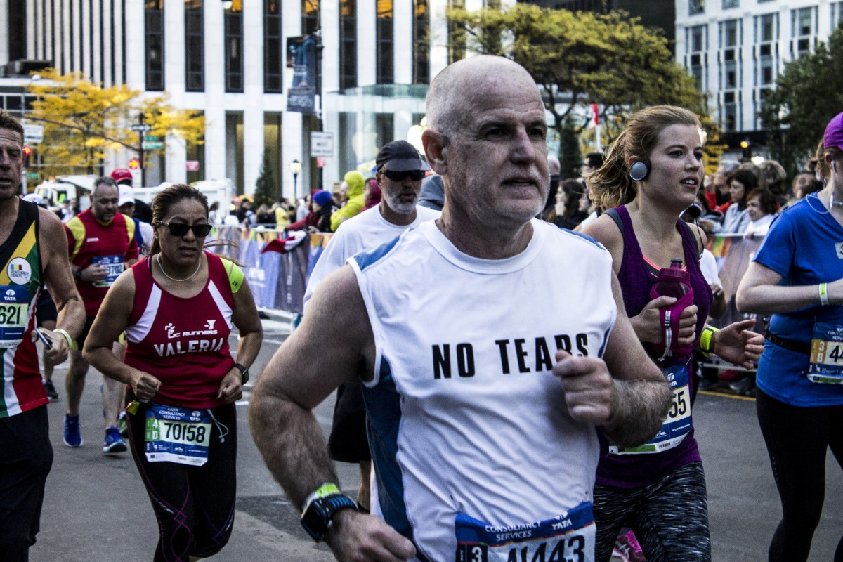 "elderly man running a marathon, with a T-shirt that says ""NO TEARS"""