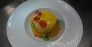 mango mousse plated with kiwi and oranges