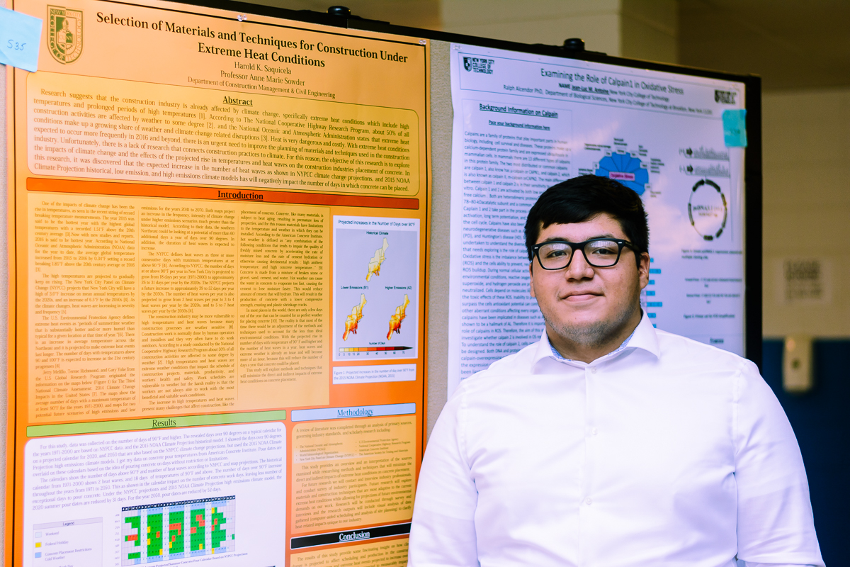 a young man with dark hair and glasses in front of an academic poster