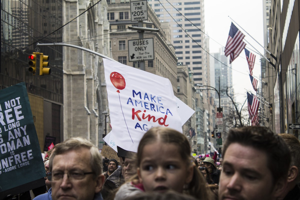 "two men holding up a young girl; protest sign says ""MAKE AMERICA KIND AGAIN"""