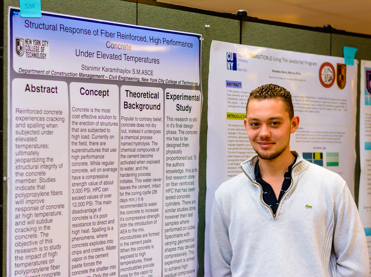 a young blond man standing in front of his academic poster