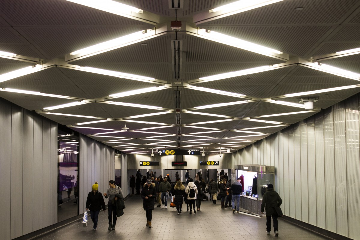 an underground subway tunnel/passageway with pedestrians and patterned lights on the ceiling