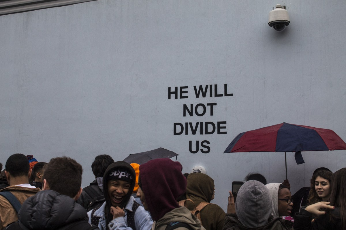people with umbrellas at art installation, in front of wall that says HE WILL NOT DIVIDE US