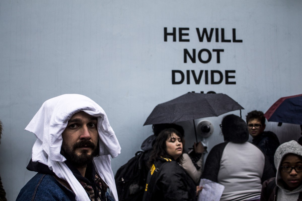 "people with umbrellas at art installation wall that says ""HE WILL NOT DIVIDE"""