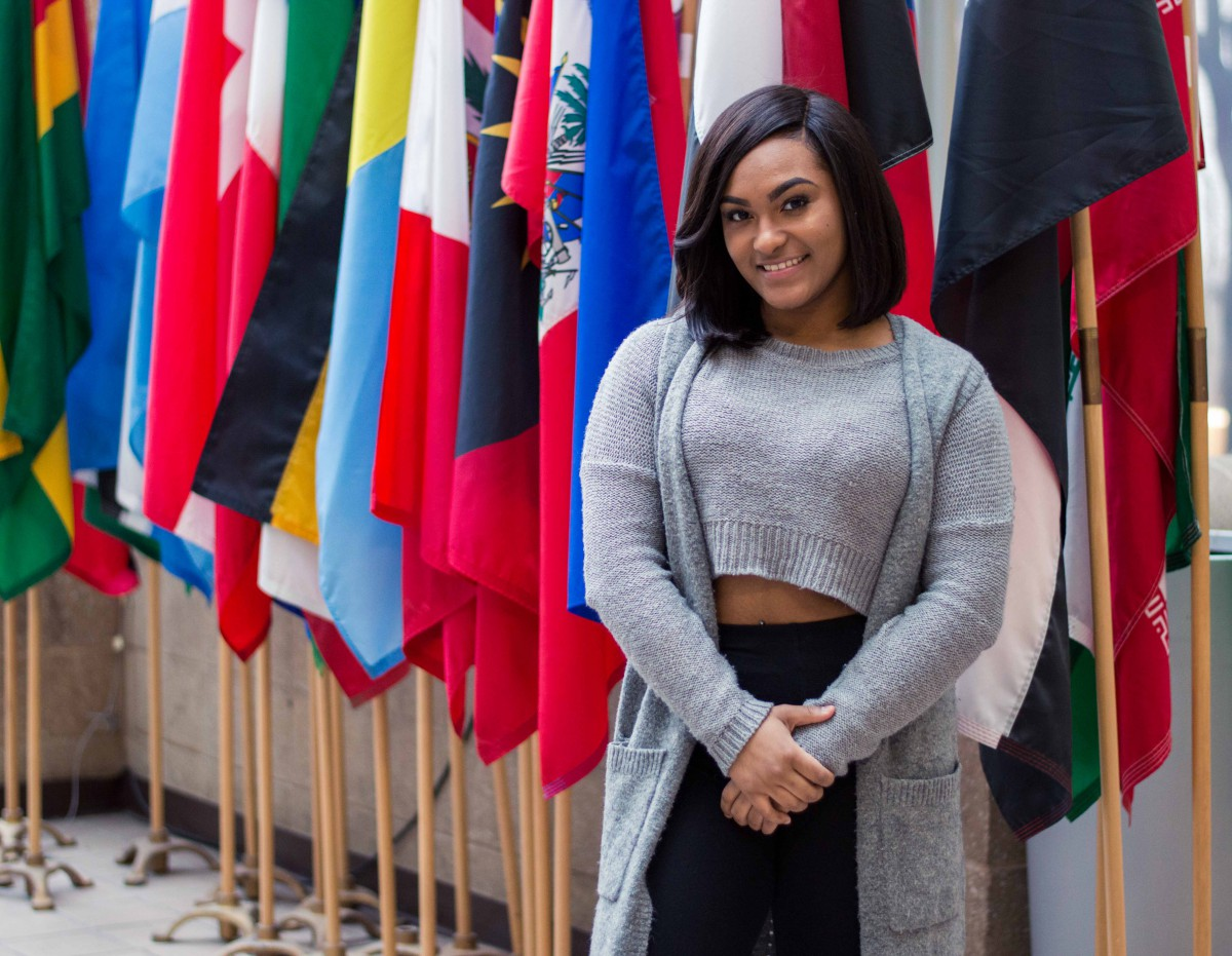 a young woman in a gray sweater, in front of colorful flags