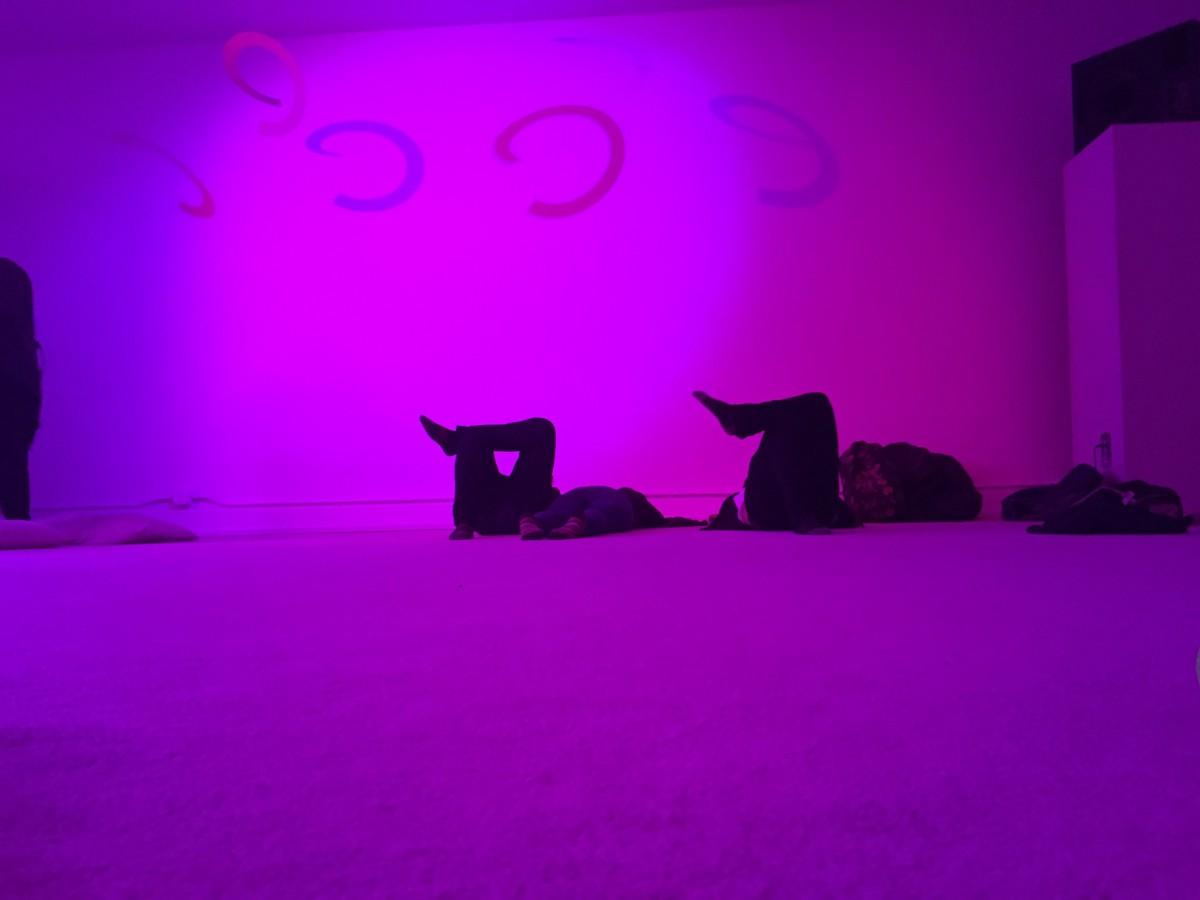 people lying down on carpet in a purple-lit room